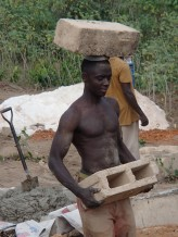 David carrying blocks for the health clinic